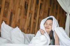 Mentira asiática da mulher do close up na cama sob a cobertura com a cara do sorriso na manhã fotos de stock