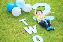 A mentira asiática feliz da criança do close up no assoalho da grama no parque textured o fundo no ò conceito do aniversário dos  imagem de stock royalty free