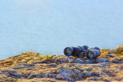 Mentira binocular do turista nas rochas sobre a montanha contra um rio azul fotos de stock