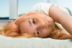 Mentira bonita del adolescente acogedora en la cama que presenta para Fotografía de archivo