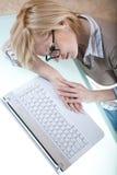 Mentira cansada al lado de la computadora portátil Foto de archivo