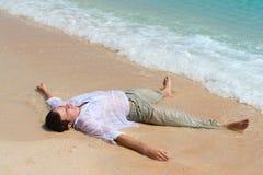 Mentira cansado do homem no Sandy Beach Imagens de Stock Royalty Free