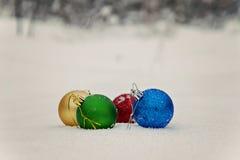 mentira coloreada de las bolas de la Navidad en la nieve Fotografía de archivo