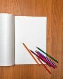 Mentira coloreada de los lápices en el cuaderno Escuela Imagen de archivo