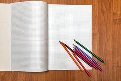 Mentira coloreada de los lápices en el cuaderno Escuela Fotos de archivo