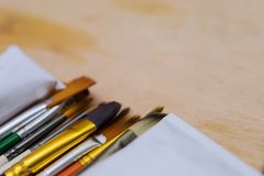 Mentira colorida artística do desenho do close-up das escovas de pintura em uma paleta de madeira imagens de stock