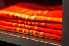 Mentira a cuadros de la tela escocesa roja en un estante polvoriento del armario Foto de archivo libre de regalías