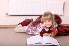 Mentira da menina no assoalho perto do radiador com livro. Fotografia de Stock