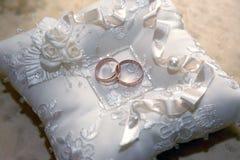 Mentira das alianças de casamento do ouro em um descanso decorativo imagens de stock