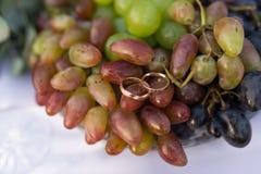 Mentira das alianças de casamento do ouro na uva Foto de Stock