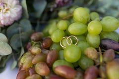 Mentira das alianças de casamento do ouro na uva Fotos de Stock
