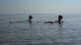 Mentira de dois homens novos na água pouco profunda Tiro Handheld vídeos de arquivo