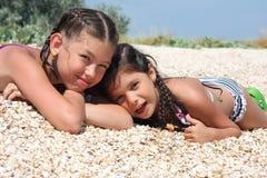 Mentira de dos muchachas en la playa Fotografía de archivo