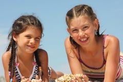 Mentira de dos muchachas en la playa Fotografía de archivo libre de regalías