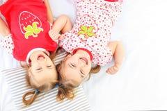 Mentira de duas crianças em uma cama dos pijamas Copie o espaço O conceito do Ch fotografia de stock