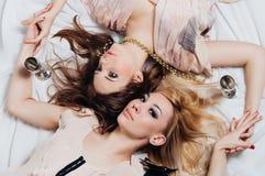 Mentira de duas meninas no assoalho entre acessórios Fotos de Stock