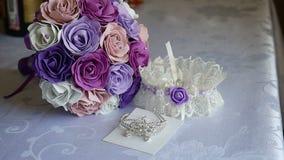 Mentira de la boda de la liga del ramo en los accesorios de la tabla dentro de la novia metrajes