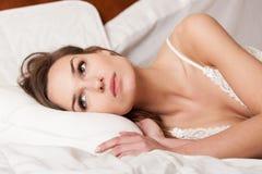 Mentira de la mujer despierta en cama imagenes de archivo