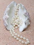 Mentira de la perla y del shell en la arena. Cierre para arriba Foto de archivo