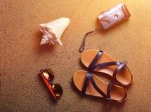 Mentira de los accesorios de la playa en la arena Cámara, sandalias, gafas de sol, conchas marinas El concepto de relajación en e Fotos de archivo