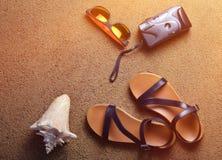 Mentira de los accesorios de la playa en la arena Cámara, sandalias, gafas de sol, conchas marinas El concepto de relajación en e Imágenes de archivo libres de regalías