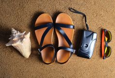 Mentira de los accesorios de la playa en la arena Cámara, sandalias, gafas de sol, conchas marinas El concepto de relajación en e Imagenes de archivo