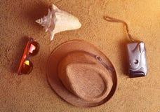 Mentira de los accesorios de la playa en la arena Sombrero, cámara, gafas de sol, cáscara El concepto de relajación en el mar ¡La Imagenes de archivo