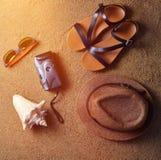 Mentira de los accesorios de la playa en la arena Sombrero, cámara, sandalias, gafas de sol, conchas marinas El concepto de relaj Imagen de archivo