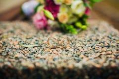 Mentira de los anillos de bodas en una piedra imagen de archivo libre de regalías