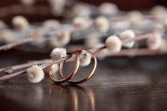Mentira de los anillos de bodas en una tabla de madera Ramitas del sauce en fondo de madera Muestras y símbolos fotografía de archivo libre de regalías