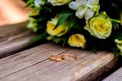 Mentira de los anillos de bodas y ramo hermoso foto de archivo