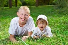 Mentira de los niños en la hierba Foto de archivo libre de regalías