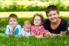 Mentira de los niños en la hierba verde Imágenes de archivo libres de regalías
