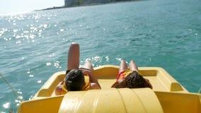 Mentira de los niños que descansa sobre un océano del mar del barco del yate los niños montan un barco del catamarán en el océano almacen de video