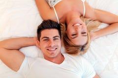 Mentira de relajación casada feliz de la pareja en cama imagen de archivo libre de regalías