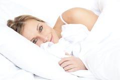 Mentira de relajación de la mujer brillante en su cama imagen de archivo