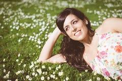 Mentira de relajación de la mujer feliz morena en hierba Fotos de archivo libres de regalías