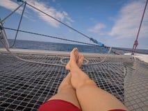 Mentira de relajación del hombre en la red de un catamarán imagenes de archivo