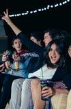 Mentira de risa de la mujer sobre sus amigos que asisten Fotografía de archivo libre de regalías