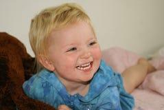 Mentira de risa del niño rubio en cama Imagenes de archivo