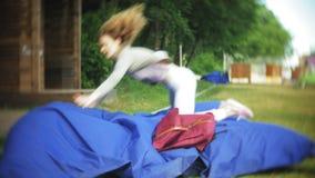 Mentira de salto de la mujer joven en un área del salón del parque en soplos suaves metrajes