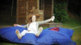 Mentira de salto de la mujer joven en un área del salón del parque en soplos suaves almacen de video