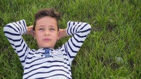 Mentira de sorriso feliz da criança na grama verde relaxado filme