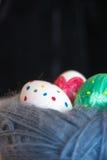 Mentira de três ovos da páscoa em um emaranhado das lãs Fotografia de Stock Royalty Free
