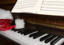 Mentira del casquillo de Papá Noel en un piano Fotos de archivo