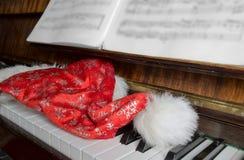 Mentira del casquillo de Papá Noel en un piano Imagen de archivo