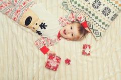 Mentira del niño pequeño en la cama con el regalo Fotos de archivo libres de regalías