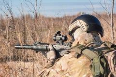 Mentira del soldado de Airsoft en la presentación con la imagen ascendente del cierre del rifle Imágenes de archivo libres de regalías