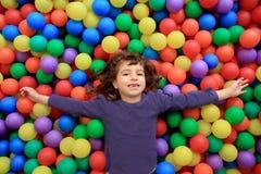 Mentira divertida de la niña del parque de las bolas coloridas Imagenes de archivo