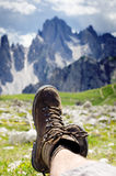 Mentira do caminhante do homem em uma terra Os picos gostam de um fundo Dia ensolarado Botas Trekking Alargamento da lente O moch imagens de stock royalty free
